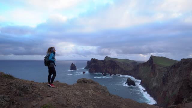 vidéos et rushes de randonneuse debout sur les rocheuses à la recherche au lever du soleil à madère - évasion du réel
