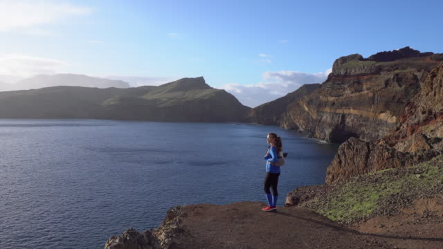Female hiker standing on rocky looking at sunrise in Madeira