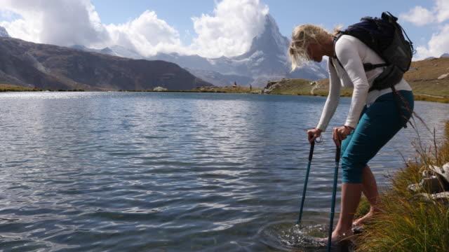 Female hiker tests water at lake edge, Matterhorn distant Matterhorn, Zermatt, Valais Canton pedal pushers stock videos & royalty-free footage