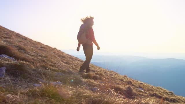 vídeos de stock, filmes e b-roll de slo mo ts caminhante fêmea andando pela grama coberta de encosta da montanha sob o sol - eslovênia