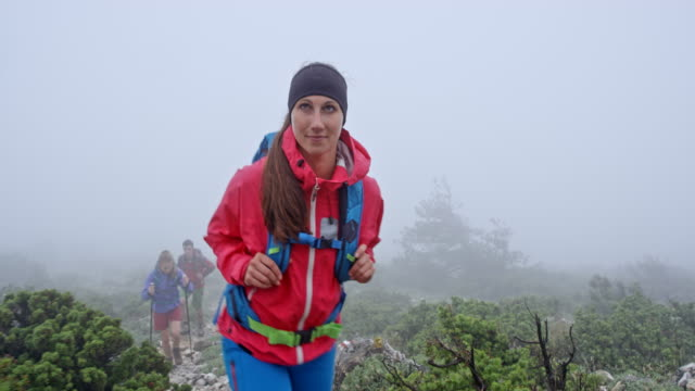 Female hiker walking up the foggy mountain with her friends video