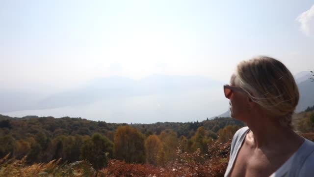 vídeos y material grabado en eventos de stock de mujer caminante camina por encima de bosques y lago, montañas - memorial day weekend