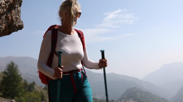 female hiker walks along path above valley, mountains - pantaloni capri video stock e b–roll