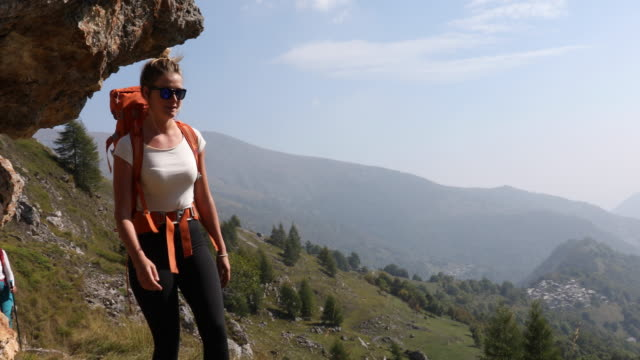 Female hiker walks along path above valley, mountains She looks off to distant scene pedal pushers stock videos & royalty-free footage