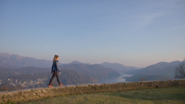 vídeos de stock e filmes b-roll de female hiker walks along stone wall, view of mountains and lake below - céu claro
