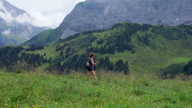 weibliche wanderer führt durch hohe gräser in alpen - einzelne frau über 30 stock-videos und b-roll-filmmaterial