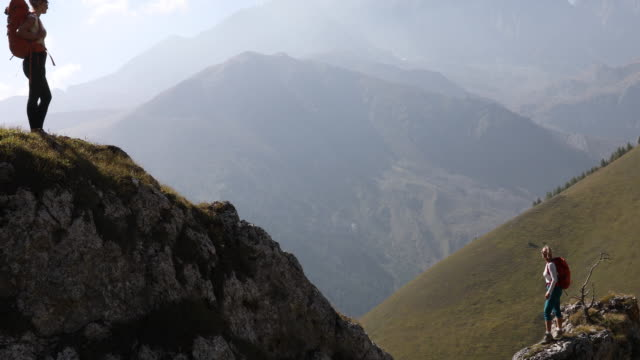 Female hikers look out form mountain ridge, above valley Mountains distant pedal pushers stock videos & royalty-free footage