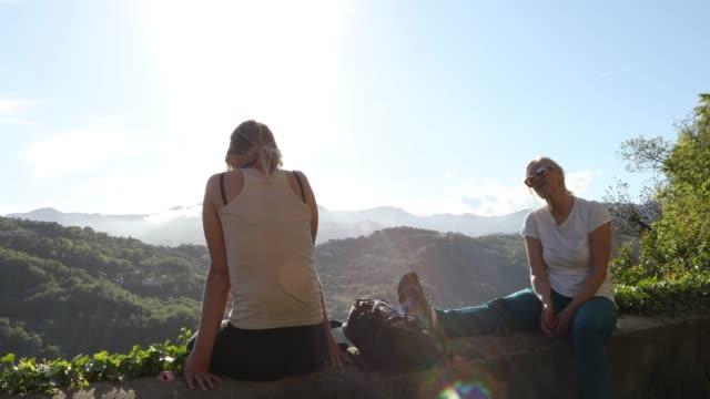 vidéos et rushes de randonneurs féminins relaxe au-dessus de la vallée au lever du soleil - évasion du réel