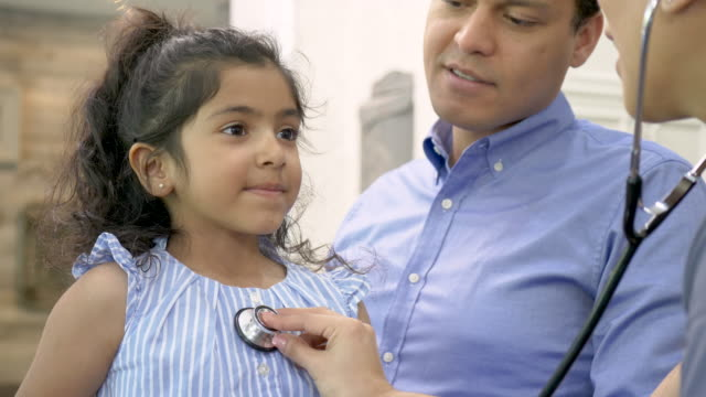 A female hispanic physician A young female child of hispanic/latino descent  is having her heart examined at home. She is smiling at the female hispanic/latino physician. She is sitting on her dads lap who is smiling down at her. The doctor is wearing scrubs and a stethoscope around her neck. general practitioner stock videos & royalty-free footage