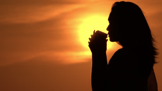 female holding cup with to go drink sun rising in the sky