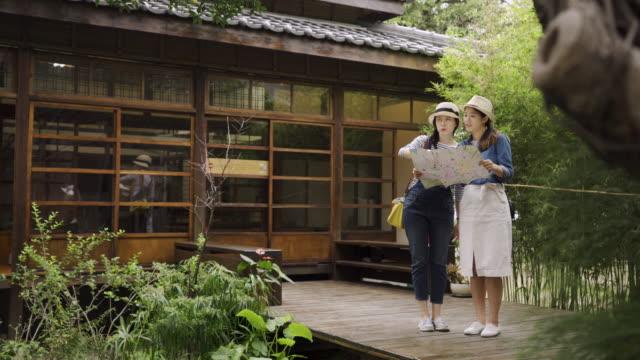 stockvideo's en b-roll-footage met vrouw houden toeristische kaart bespreken - raam bezoek