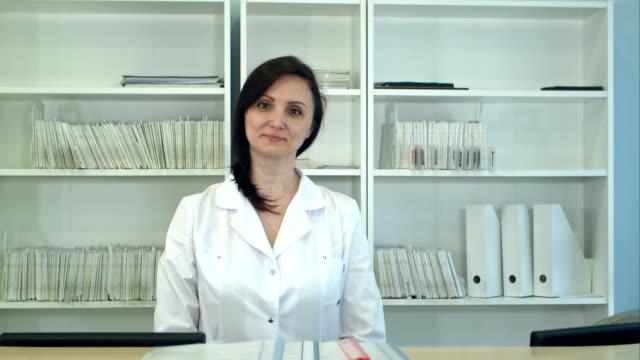 Réceptionniste d'hôpital femme regardant la caméra - Vidéo