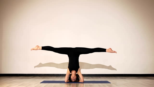 Female in black clothes doing headstand splits in yoga room Female in black clothes doing headstand splits in yoga room doing the splits stock videos & royalty-free footage