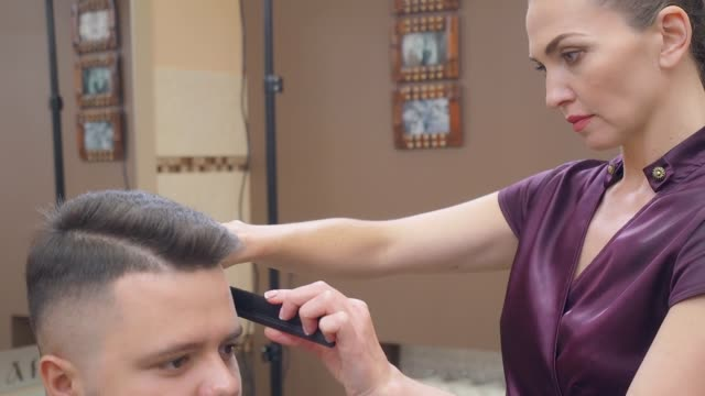 Female in dark red dress cutting hair with scissor and black comb, close shot. Man in hairdressing saloon. Interior of barbershop. Female in dark red dress cutting hair with scissor and black comb, close shot. Man in hairdressing saloon. Interior of barbershop. Selective soft focus. Blurred background russian ethnicity stock videos & royalty-free footage