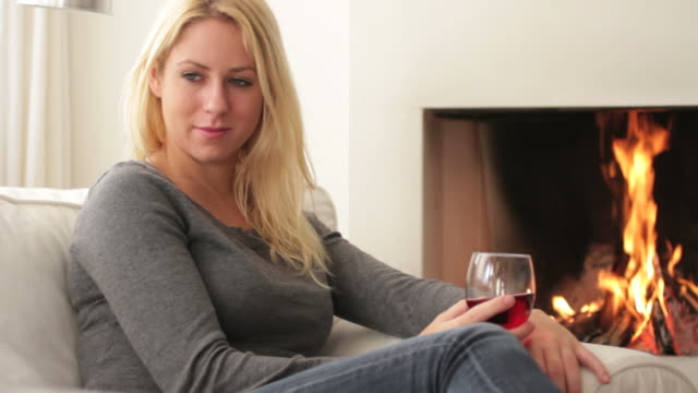 Female in front of fireplace drinking wine video
