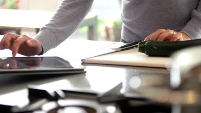 Female in kitchen preparing food and look at digital tablet video