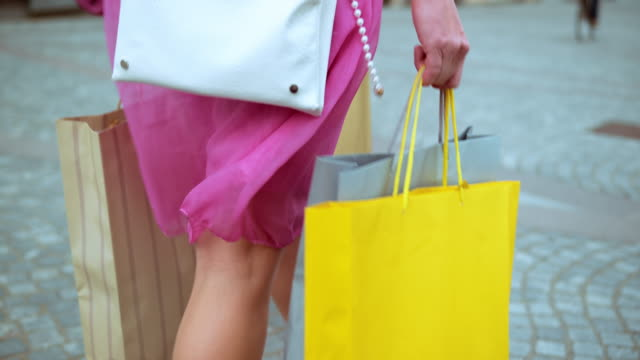 SLO MO Female in pink dress walking with shopping bags Slow motion medium tracking shot of a woman in pink dress walking down the street in high heels carrying shopping bags in her hands. dress stock videos & royalty-free footage