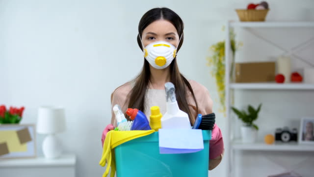 female in respirator holding basket with household chemicals, health risk - disinfectant stock videos & royalty-free footage