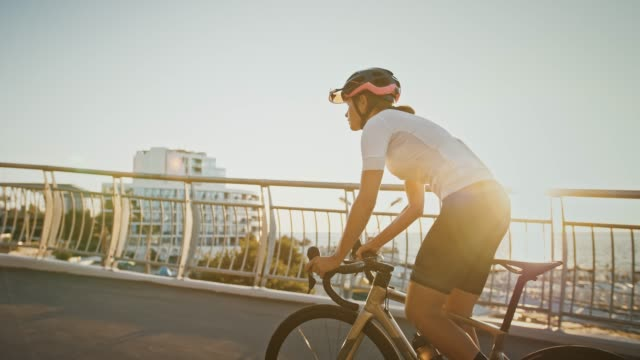 Female in sportswear and protective helmet is riding a sports bike uphill along bridge, near a sea coast. Close up, cinematic