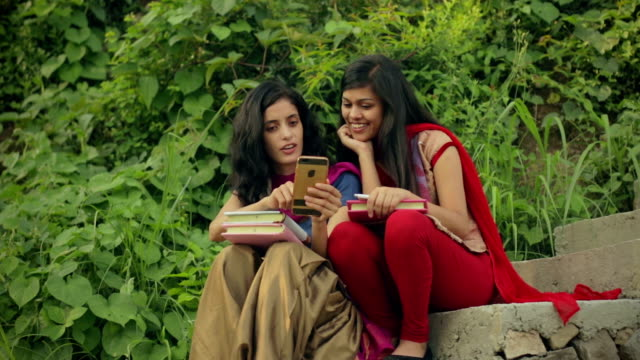 female indian students sharing smart phone. - two students together asian video stock e b–roll