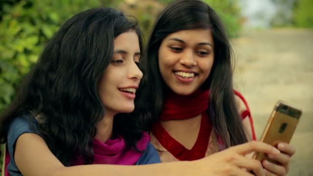 Female Indian students sharing smart phone. video