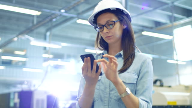 Female Industrial Engineer in a Hard Hat Uses Smartphone while Standing in Big Factory. video
