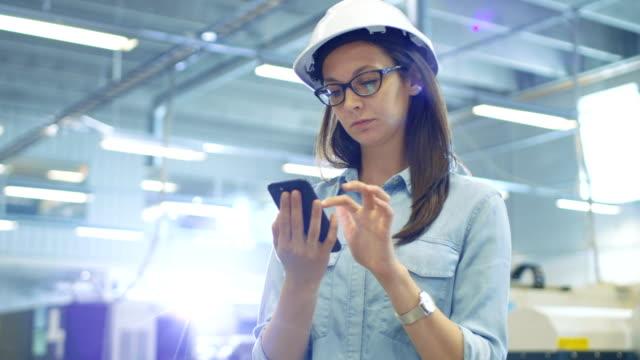 kvinnliga industriell ingenjör i en hård hatt använder smartphone samtidigt står i stora fabriken. - industrial connectivity bildbanksvideor och videomaterial från bakom kulisserna
