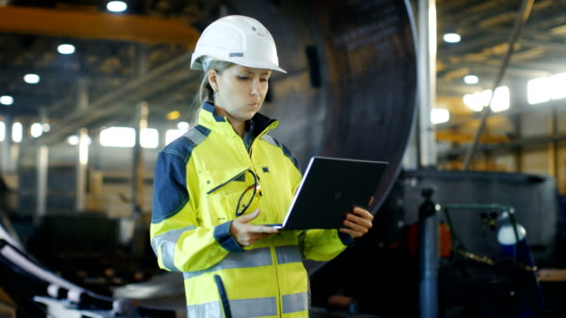 Female Industrial Engineer in the Hard Hat and Safety Jacket Uses Laptop Computer while Standing in the Heavy Industry Manufacturing Factory. In the Background Various Metalwork Project Parts Lying video