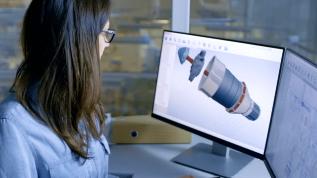 female industrial engineer works on 3d turbine/engine model in cad software on her desktop computer. inside of the factory is seen from her office window. - designers video stock e b–roll