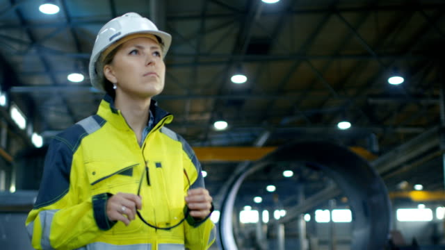 female industrial worker in the hard hat puts on protective goggles while walking through heavy industry manufacturing factory. in the background various metalwork components are seen. - occhiali protettivi video stock e b–roll