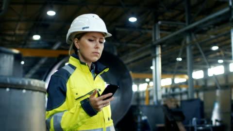 kadın sanayi işçisi kask içinde cep telefonu ağır sanayi ile fabrika üretim yürürken kullanır. arka planda çeşitli metal işi proje yalan parçaları - dişiler stok videoları ve detay görüntü çekimi