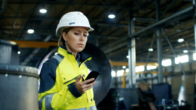 Female Industrial Worker in the Hard Hat Uses Mobile Phone While Walking Through Heavy Industry Manufacturing Factory. In the Background Various Metalwork Project Parts Lying Female Industrial Worker in the Hard Hat Uses Mobile Phone While Walking Through Heavy Industry Manufacturing Factory. In the Background Various Metalwork Project Parts Lying  Shot on RED EPIC-W 8K Helium Cinema Camera. quality control stock videos & royalty-free footage
