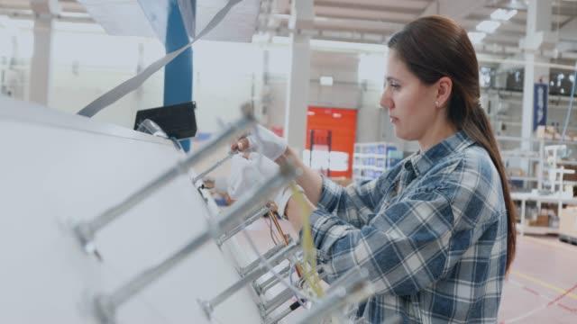 kvinnliga industri arbetare som arbetar med tillverknings utrustning i en fabrik - maskindel bildbanksvideor och videomaterial från bakom kulisserna