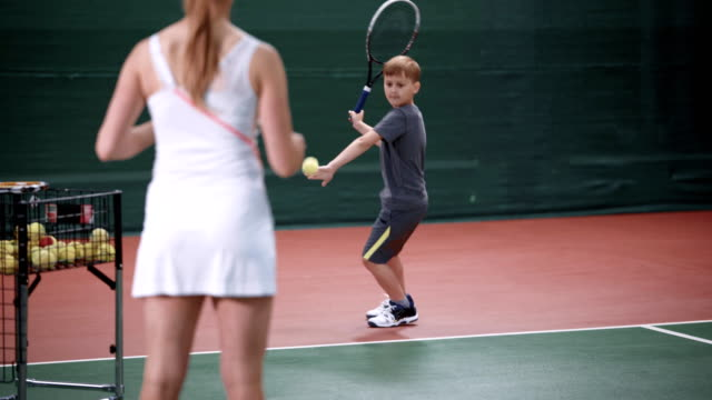 Female instructor teaching little boy playing tennis. Woman in white sport outfit standing in the court throwing yellow balls to child. Young sportsman learning to return tennis-ball with a racket video