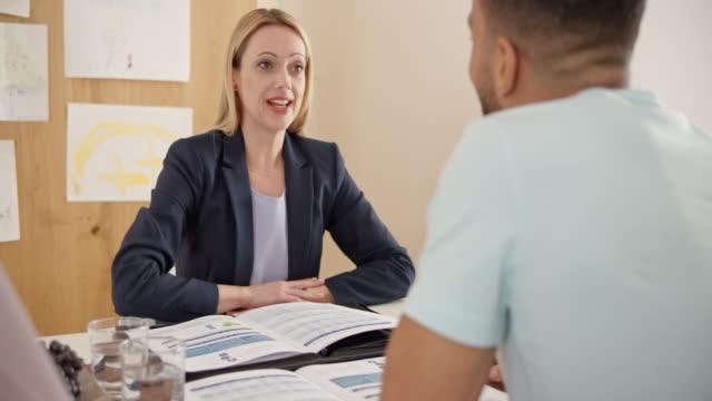 vidéos et rushes de agente d'assurance conseille un client à la maison - expliquer