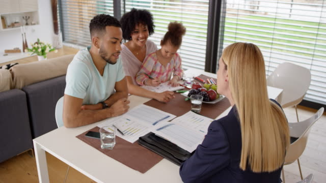 Female insurance agent advising young couple at their home video