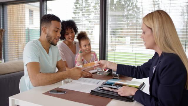 vídeos de stock, filmes e b-roll de agente de seguros feminino, cumprimentando-se com a família em sua casa - dia do cliente