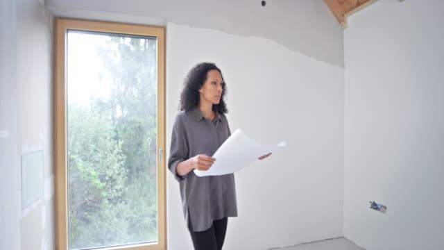 architetto d'interni femminile che tiene piani mentre cammina nell'edificio - architetto video stock e b–roll