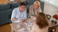 istock Female interior designer advising a senior couple in their home 666088664