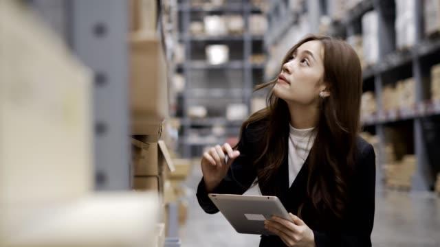 stockvideo's en b-roll-footage met vrouwelijke inventory manager controleert voorraad, pakketten, pakketten klaar voor verzending. - buiten de vs