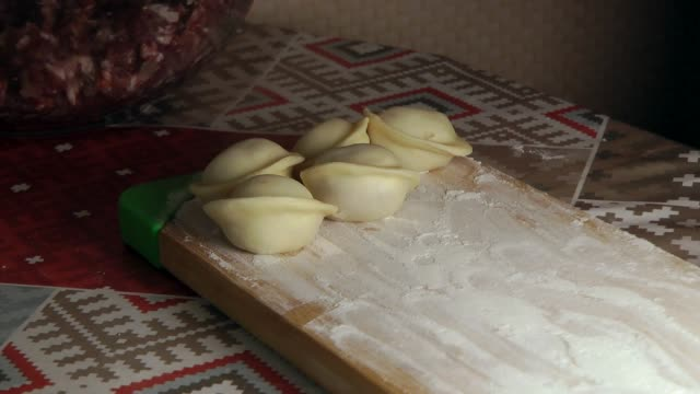 A female is shaping the dough with meat inside to make dumplings video