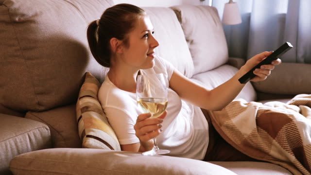 female is watching TV and sitting with white wine video