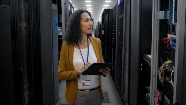 stockvideo's en b-roll-footage met vrouwelijke ingenieur het controleren van de servers in de serverruimte - men blazer
