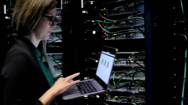 stockvideo's en b-roll-footage met vrouwelijke it engineer binnenkomen serverkamer met haar laptop - datacenter