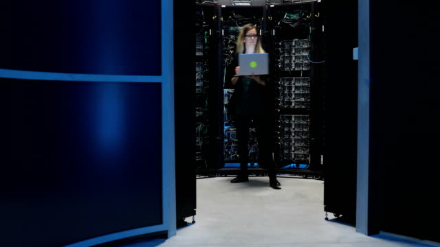 Female IT Engineer Working in Server Room with her Laptop Female IT Engineer Working in Server Room with her Laptop. server room stock videos & royalty-free footage