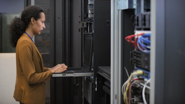 ds female it engineer working on a laptop in the server room - supporto tecnico video stock e b–roll