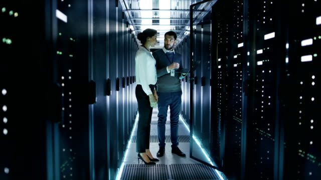 Female IT Technician and Male Server Engineer Discussing Settings of a Working Data Center. Man Holds Laptop They Stand Before Open Rack Server.