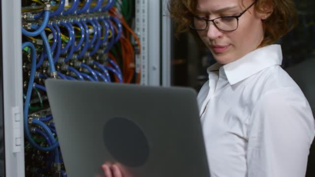 kvinnlig it-tekniker testa server utrustning med laptop - server room bildbanksvideor och videomaterial från bakom kulisserna