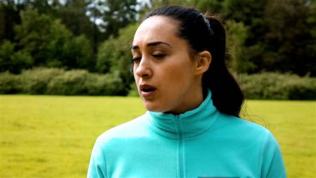 Female jogger out of breath looks around with a subtle smile on her face in slow motion video