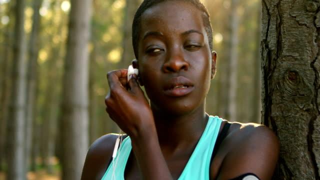 Female jogger putting headphone in her ear 4k